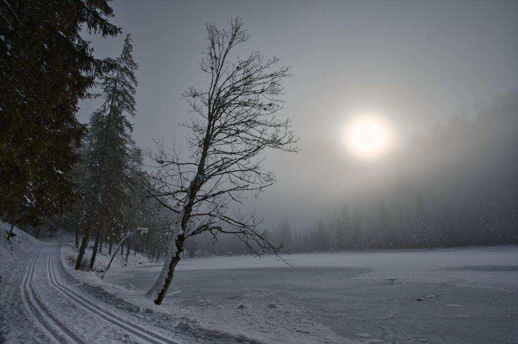 Winter sun through fog, over a frozen lake in Austria